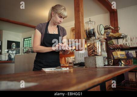Boutique femme assistant à l'aide d'écran tactile de digital tablet in country store Banque D'Images