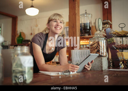 Femme shop assistant with digital tablet in country store Banque D'Images