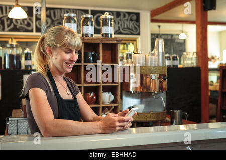 Femme shop assistant texting on smartphone in country store cafe Banque D'Images