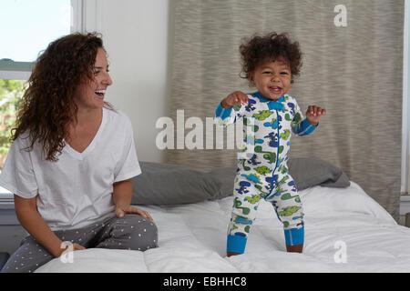 Jeune femme regardant petit garçon jumping on bed Banque D'Images