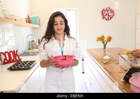 Adolescente en tablier blanc gâteau de cuisson dans la cuisine Banque D'Images