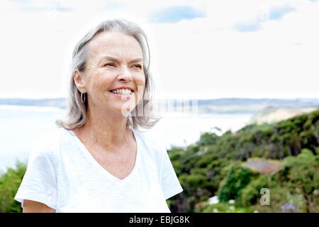 Senior woman, de l'océan en arrière-plan, Raglan, Nouvelle-Zélande