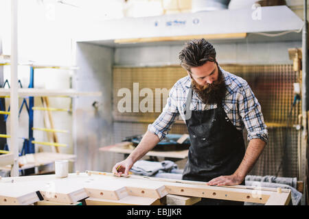 Cropped shot of mid adult craftsman mesurant en bois atelier d'organes Banque D'Images