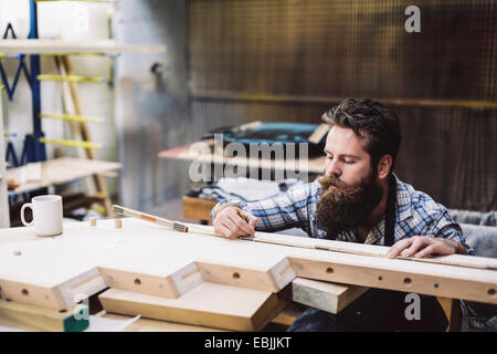 Cropped shot of mid adult artisan bois de mesure en atelier d'éléments Banque D'Images