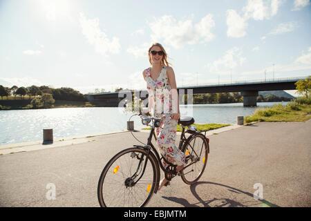 Jeune femme à vélo le long de la rivière, l'île du Danube, Vienne, Autriche