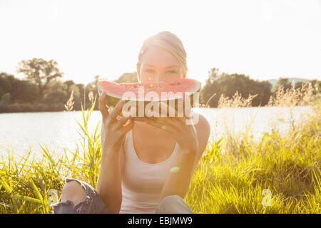Portrait of young woman holding up tranche de melon en face de face, l'île du Danube, Vienne, Autriche Banque D'Images