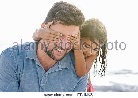 Fille aux mains couvrant les yeux des pères sur plage, Toscane, Italie Banque D'Images