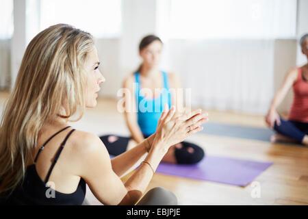 Femelle adulte tuteur avec les mains ensemble en classe de pilates Banque D'Images