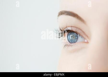 Studio portrait of mid adult womans gazing blue eye Banque D'Images