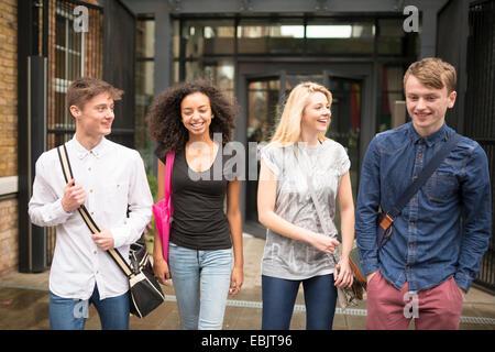 Quatre amis marchant et souriant Banque D'Images