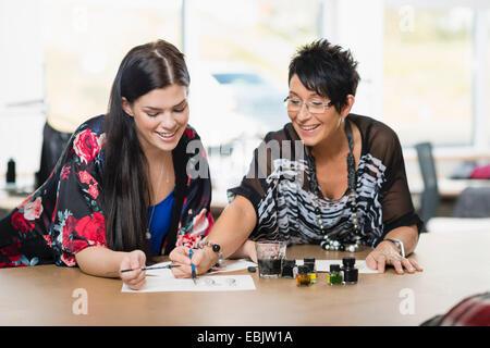 Deux couturières peinture dessin de mode sur table de travail Banque D'Images