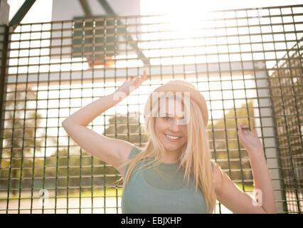 Portrait de jeune joueur de basket-ball féminin la maintenant sur grillage