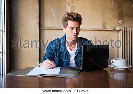 Young male student sitting at cafe table à l'aide d'ordinateur portable et la prise de notes Banque D'Images