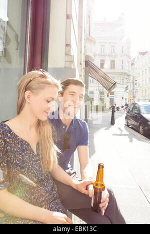 Young couple at sidewalk cafe boire de la bière Banque D'Images