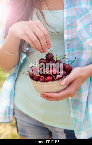 Close up of young woman with bowl of cherries Banque D'Images