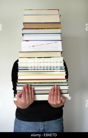 Femme portant une pile de livres Banque D'Images