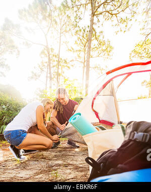 USA, Floride, Tequesta, Couple setting up tent in forest Banque D'Images