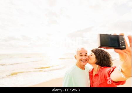 USA, Floride, Jupiter, couple sur la plage au lever du soleil selfies Banque D'Images