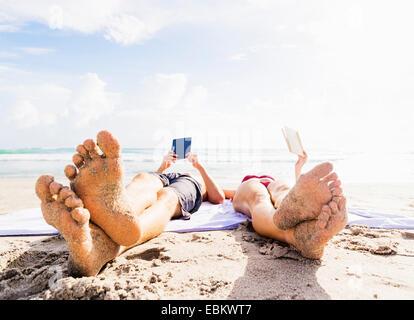 USA, Floride, Jupiter, Close-up de sable-couverts pieds de jeune couple lying on blanket sur lecture de plage Banque D'Images