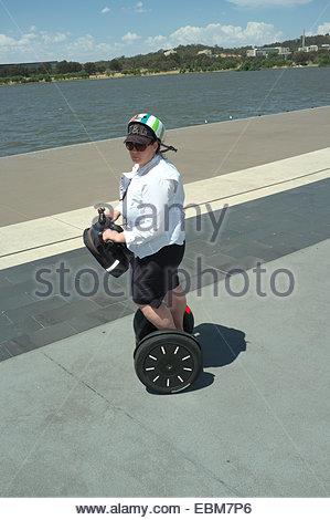 Une femme passe le lac Burley Griffin sur un transporteur personnel Segway (PT), Canberra, Territoire de la capitale Banque D'Images