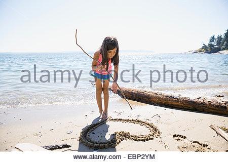 Girl drawing heart-shape dans le sable sur la plage Banque D'Images