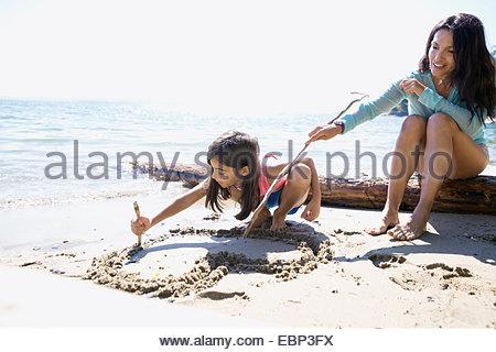 Mère et fille coeur dessin-forme dans le sable Banque D'Images