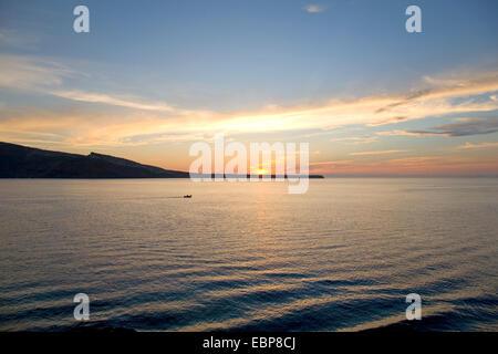 Ia, Santorin, Grèce, sud de la Mer Egée. Vue sur mer à l'île de Thirasia et le coucher du soleil, petit bateau qui Banque D'Images