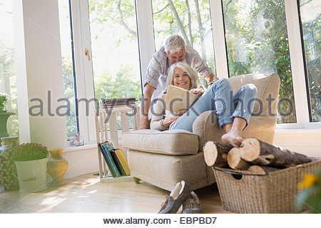 Senior couple reading book in armchair Banque D'Images
