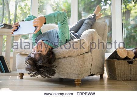 Boy using digital tablet la tête en bas dans un fauteuil Banque D'Images
