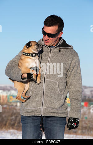 Man holding Bugg (croisement entre Boston Terrier Pug) et dog in city park Banque D'Images