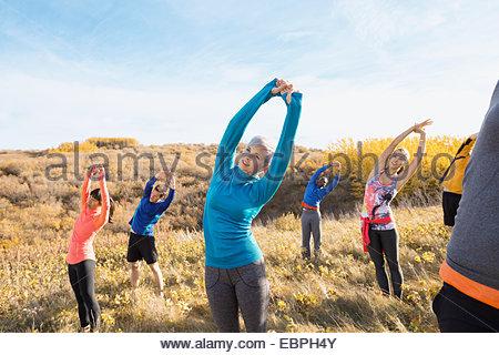 Le conditionnement physique en groupe s'étend à sunny rural field Banque D'Images