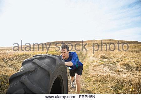En poussant l'homme dans la ville ensoleillée de pneu crossfit rural field Banque D'Images