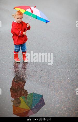Petite fille en vêtements de pluie avec parapluie ouvert Banque D'Images