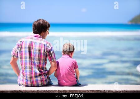 Père et son fils assis sur le mur et la vue sur la mer, vue arrière Banque D'Images