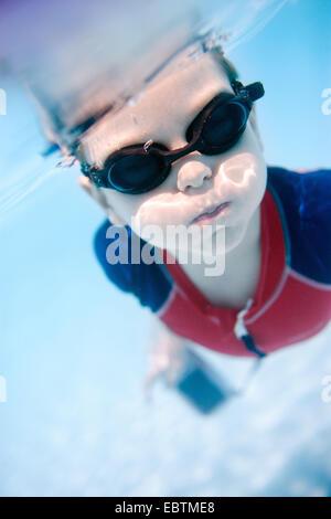 Petit garçon portant des lunettes de natation plongée sous-marine avec une caméra sous-marine dans les mains Banque D'Images