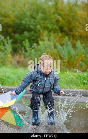 Petit garçon sautant avec des bottes de pluie dans une flaque Banque D'Images