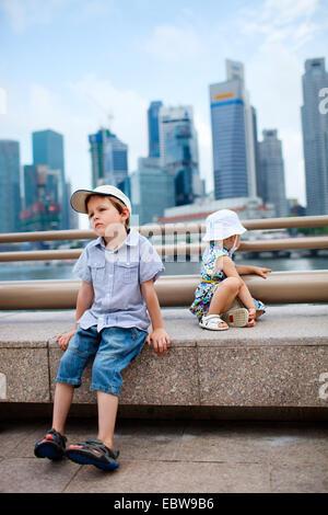 Deux petits enfants assis en centre-ville, Singapour, Singapour
