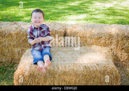 Cute Young Mixed Race Boy having fun on Hay Bale à l'extérieur. Banque D'Images