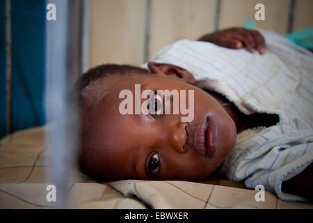 Petite fille au lit avec une mouche de ramper sur son visage, au Burundi, Bujumbura, Bujumbura Marie Banque D'Images