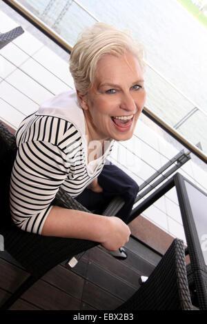 Belle femme aux cheveux blancs tournant autour d'un café en riant de président de l'appareil photo, l'Allemagne, Banque D'Images