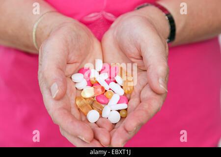 Vieille Femme tenant une sélection de prescription et de compléter des pilules dans la paume de ses deux mains. Banque D'Images
