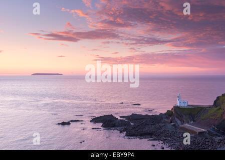Hartland Point Lighthouse et Lundy Island sous un soleil colorés, North Devon, Angleterre. Printemps (mai) 2014. Banque D'Images