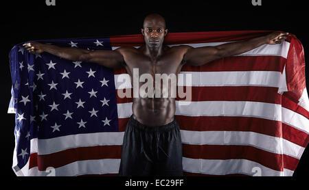 Portrait de l'homme musclé holding American flag sur fond noir. Torse nu masculin man United S Banque D'Images