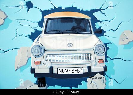 Voiture trabant est-allemande à travers le mur de Berlin dirving. graffiti sur east side gallery berlin. Banque D'Images