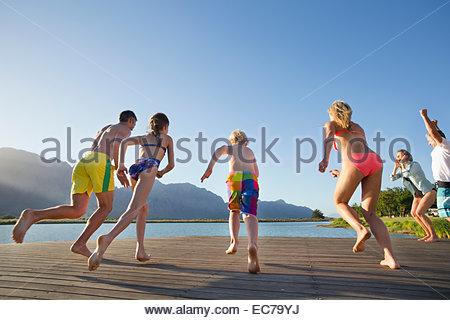 Multi generation family running à sauter dans le lac à partir d'une jetée Banque D'Images