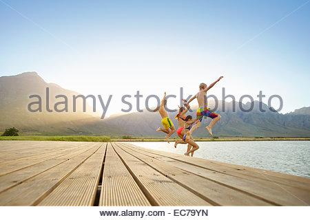 Famille, en maillot de bain, sauter dans un lac d'une jetée Banque D'Images