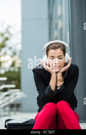 Jeune femme aux yeux clos assis dans les escaliers avec un casque de musique audition Banque D'Images