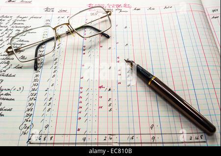 Un vieux livre de comptes, les figures en livres, shillings et pence avec stylo et verres Banque D'Images