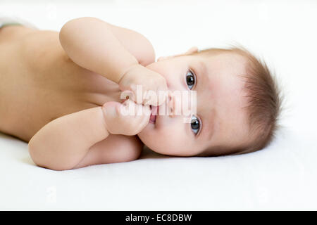 Funny baby boy lying on bed blanc piscine Banque D'Images