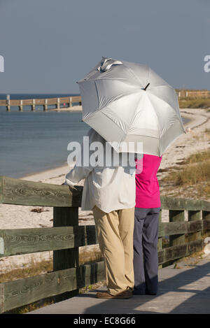 La protection UV vacancier holding umbrella le long de la côte de Floride USA Banque D'Images